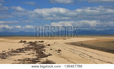 Driftwood at Marahau beach. Low tide. Mountains and summer clouds.