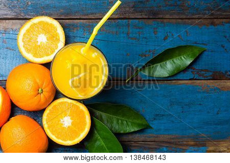 Glass of freshly squeezed orange juice and fresh oranges and leaves on wooden blue background. Top view