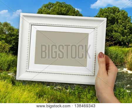 Wooden frame in beautiful woman hands on the forest background