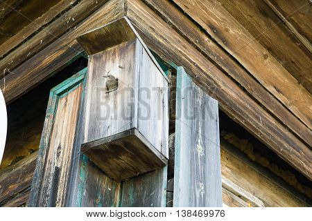 A bird in a wooden birdhouse on the wall of a building
