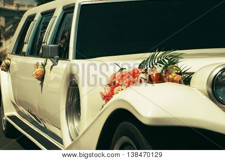 White wedding limousine decorated with flowers.