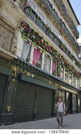 PORTO, PORTUGAL - AUGUST 10, 2016: A man speaking by mobile at the street of Flowers in the historical city of Porto Portugal.