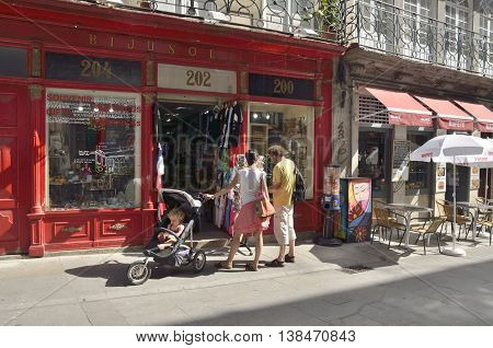 PORTO, PORTUGAL - AUGUST 10, 2016: A couple with a baby in front of a gifts shop at the street of Flowers in the historical city of Porto Portugal.