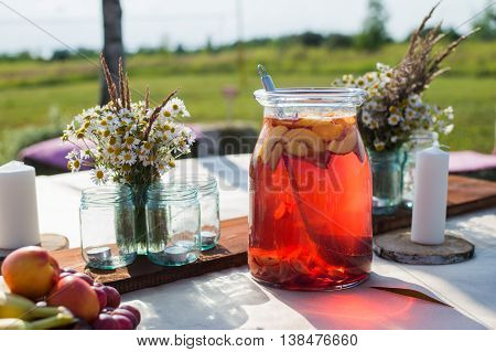 Fresh compote, fruits and flowers on wooden table closeup. Selective focus. Beutiful decoration in boho style