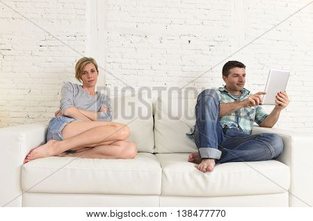 young attractive couple husband and wife at home living room couch with happy man using internet app on digital tablet pad ignoring bored and sad woman in social network addiction concept