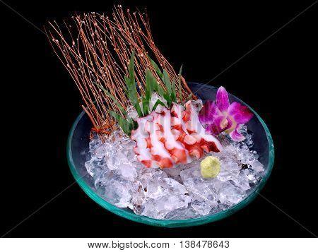 Japanese octopus tako sashimi serve on ice photo in studio lighting.