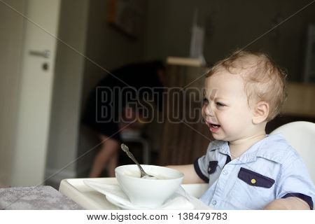 Child crying at the dinner table in cafe
