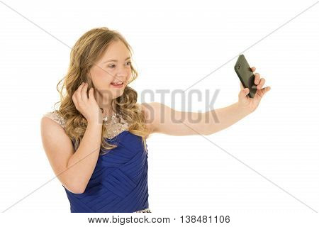 A woman with down syndrome holding out her phone taking a picture wtih a big smile
