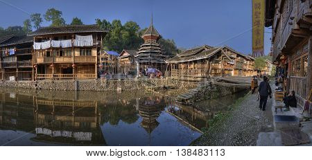 Zhaoxing Dong Village Guizhou Province China - April 8 2010: Spring sunny morning in countryside ethnic minorities wooden house and drum tower reflected in water of river rural panoramic photo.