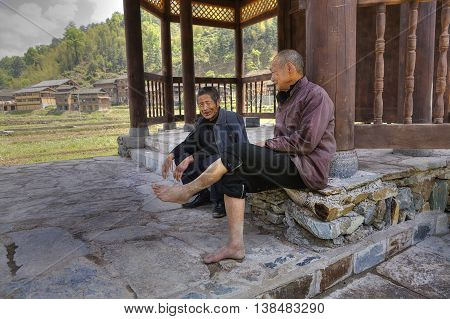 Zhaoxing Dong Village Guizhou Province China - April 8 2010: Two elderly Asian men resting in the shade under the roof of a covered bridge near the village of ethnic minorities.
