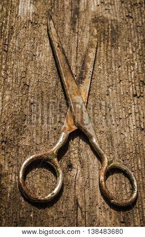 Retro vintage grunge scissors on the wooden background