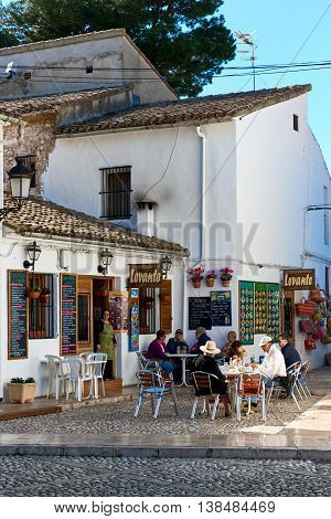 Guadalest Spain- February 2 2016: Tourists sitting in a sidewalk cafe in the Guadalest village. Guadalest is a most visited village in Spain