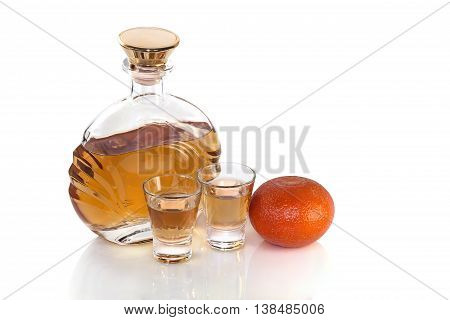 Bottle with glasses of tequila and tangerine on white background