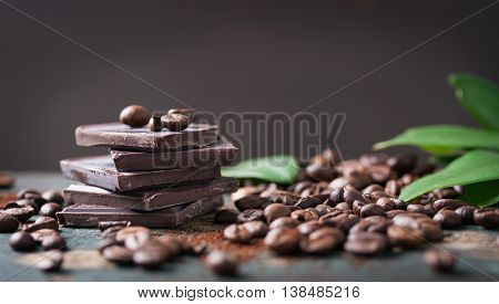 Stack of chocolate chunks with coffee beans on a wooden background horizontal with copy space