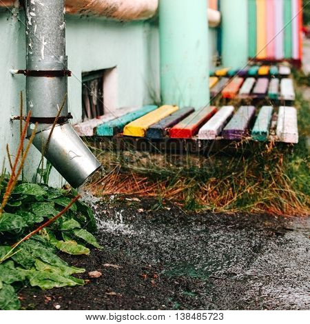 Rain water flows from metal downspout. Concept of downpours protection.