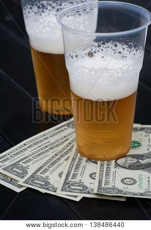 Two glasses of beer and fan-shaped dollars