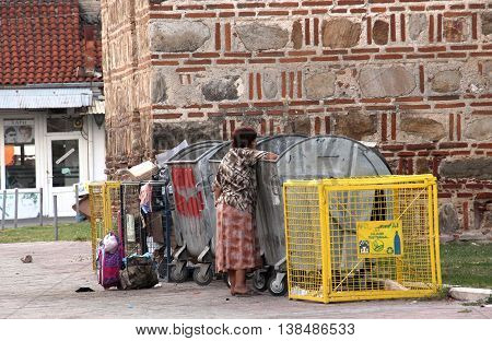 PRILEP,MACEDONIA - JULY 13 2016 : Poor Roma woman looking for discarded food in a rubbish can in the street . Picture taken in city of Prilep Macedoniaon july 132016