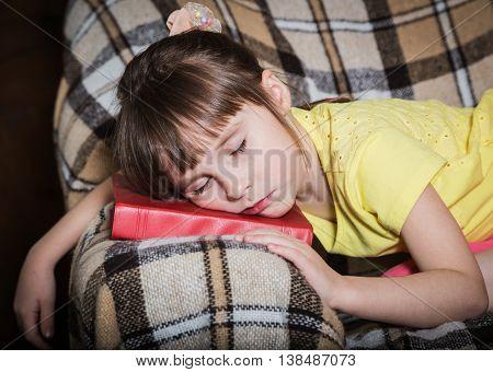 The little girl fell asleep with a book under his head