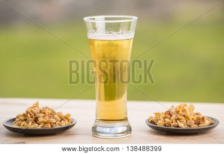 Cold beer with roasted peanuts, on wooden table, outdoor