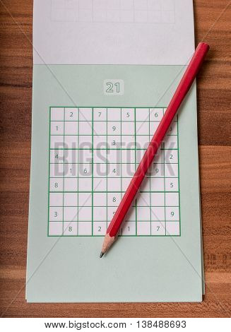 Notepad With Sudoku Crosswords And Red Pencil.