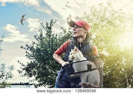 Young woman on bike with a cat in a basket standing on road and looking to somewhere.