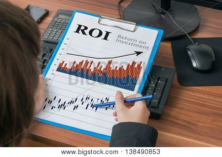 Business Woman Is Analysing Roi (return On Investment).