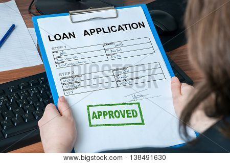Business woman is holding loan application with approved stamp.