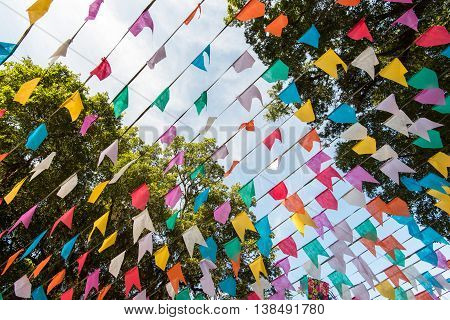 Bunting colorful flags in blue sky under trees