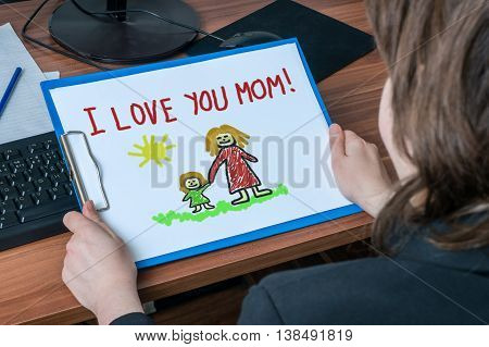 Business woman (mother) in office holds greeting card from her child with drawing and message I Love You Mom.