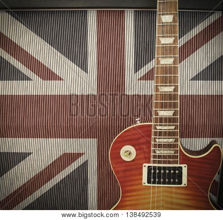 British Rock Invasion concept - detail close up of a guitar leaning against an amplifier with British Union Jack flag on the cabinet on stage at a concert - vintage toned Instagram style