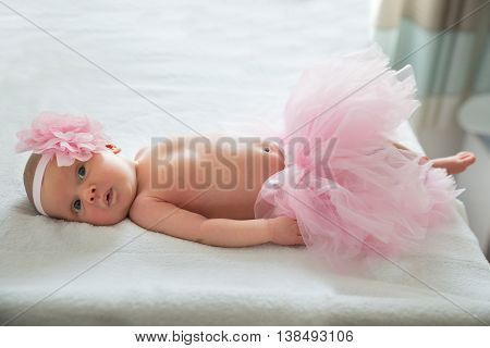 Baby Girl With Pink Tutu And Headband Lying On Bed