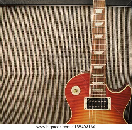 detail close up of a guitar leaning against an amplifier cabinet on stage at a concert - vintage toned Instagram style