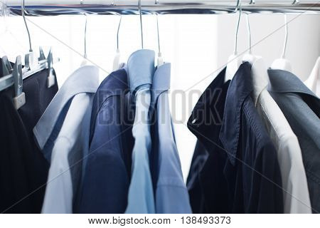 Set of male elegant shirts hanging on a rack businessman outfit and wardrobe