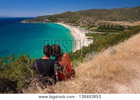 A romantic couple enjoying a magnificent sea view with beach from above. Location Solanas Beach Sardinia Italy.