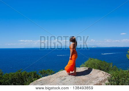 A woman in an orange long dress staying on the cliff and enjoying sea view. Location Sardinia Italy.