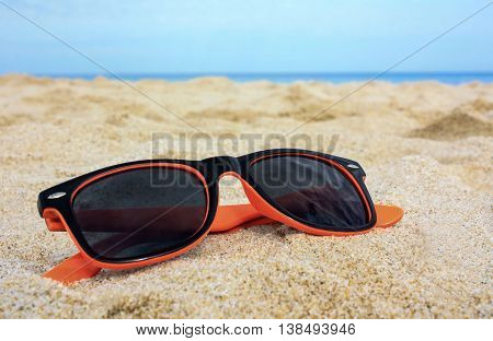 Orange-black sun-glasses on the golden sand with the sea blue water and sky on the background. Location Costa Rei Sardinia Italy.