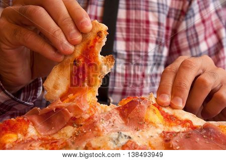 Hands of a man breaking off a piece of an italian pizza. On the background his checkered shirt.