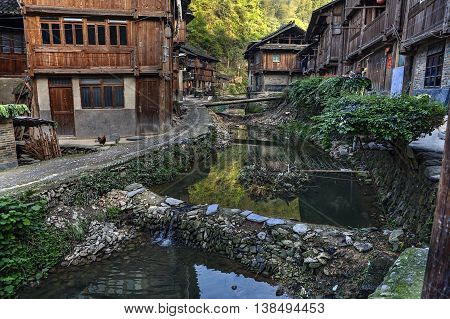 Dam on a rural river flowing between the wooden houses countryside of ethnic minorities in mountainous areas, Zhaoxing Dong Village Guizhou Province China.