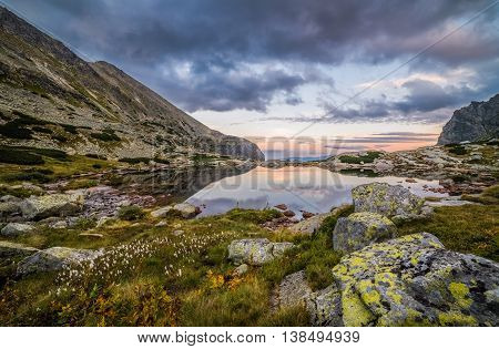 Mountain Lake Above Skok Waterfall with Rocks in Foreground at Sunset. Mlynicka Valley High Tatra Slovakia.