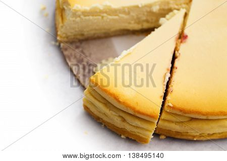 homemade cheesecake with a sliced piece the background with copy space fades to white view from above selected focus and very narrow depth of field