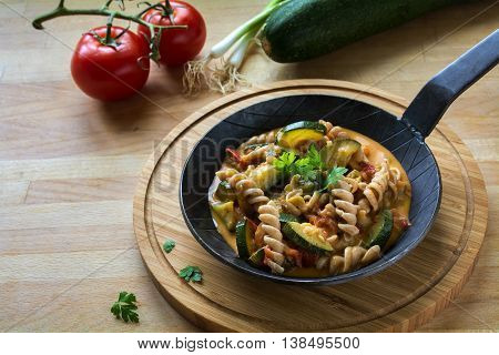 Vegetables with whole grain pasta in a rustic pan on a wooden kitchen board healthy vegetarian meal to lose weight with zucchini; tomatoes and spring onions copy space selected focus narrow depth of field