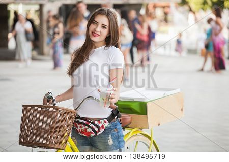 Beautiful girl on bike with freezer holds a cocktail in hands and smiling