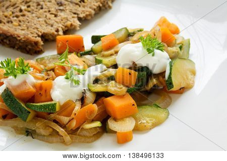 summer vegetables from zucchini and carrots with soured cream and parsley garnish plus a slice of whole grain bread a light and healthy dish on a white plate closeup with selected focus and narrow depth of field