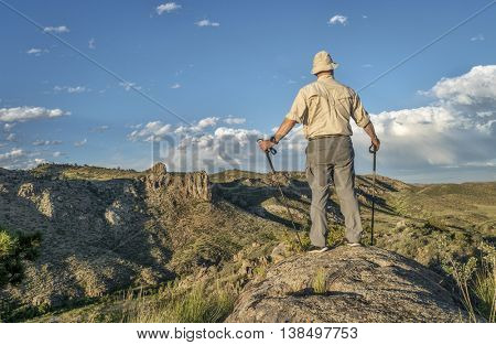 male hiker with trekking poles overlooking a mountain valley in northern Colorado - Poudre River North Fork above Halligan Reservoir