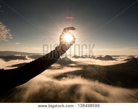 Man Hand Touch Sun. Misty Daybreak In A Beautiful Hills.