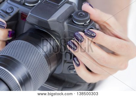 single-lens reflex camera in the hands of a girl with beautiful manicure