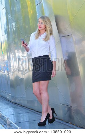 Young businesswpman checking messages on her smart phone in the city