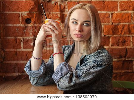 Young Blonde Woman Holding Orange Paper Cup With Cocktail Straw Sitting Near Window Against Red Bric
