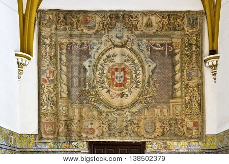 SEVILLE, SPAIN - September 12, 2015: Tapestry with the coat of arms of Queen Isabella of Portugal at the Sala de las Fiestas in the gothic palace of the Alcazar of Seville on September 12, 2015 in Seville, Spain
