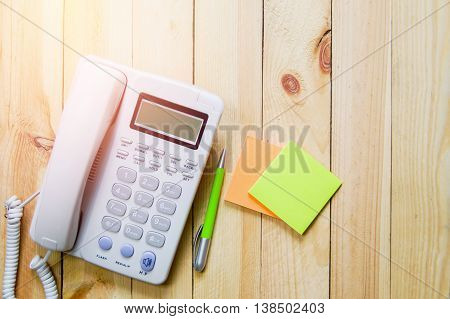 Office phone paper note and pen. Business phone and customer contact assistance concept